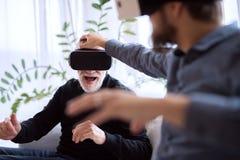 Modnisia syn i jego starszy ojciec z VR gogle w domu Fotografia Royalty Free