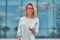Modny żeński blogger w elegancki odzieżowym i szkłach z torebką, chwyty smartphone, stoi przeciw a zdjęcie stock