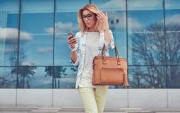 Modny żeński blogger w elegancki odzieżowym i szkłach z torebką, chwyty smartphone, stoi przeciw a fotografia royalty free