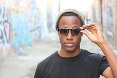 Modny Afrykański mężczyzna być ubranym okulary przeciwsłoneczni, beanie, przebijanie i czarny trójnik nad miastowym tłem, Zdjęcie Stock