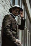 Modny amerykanin afrykańskiego pochodzenia biznesmen jest ubranym fedora kapelusz pozuje budować okulary przeciwsłonecznych i zdjęcie stock
