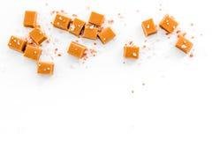 Modny deser Solony karmel Karmel sześciany kropiący solankowymi kryształami na białej tło odgórnego widoku przestrzeni dla teksta obraz stock
