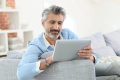 Modny dorośleć mężczyzna dosłania emaila z cyfrową pastylką Fotografia Stock