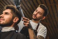 Modny fryzjer męski robi ostrzyżeniu indoors Zdjęcie Royalty Free