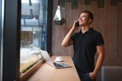 Modny i elegancki młody człowiek opowiada na telefonie, relaksuje z kawą fotografia stock