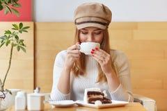Modny młody piękny żeński projektant przerwę po pracy, odwiedza lokalnego bufet, pije gorącego napój, trzyma białego kubek, zdjęcie stock