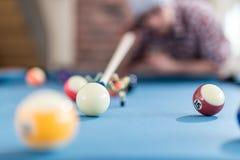 Modny mężczyzna przygotowywa uderzać białą piłkę z billiards gromadzi snooker wskazówkę obraz royalty free