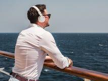 Modny mężczyzna słucha muzyka w białych hełmofonach fotografia stock