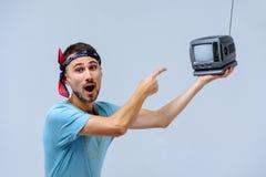 Modny mężczyzna w jaskrawych spodniach z małym TV manifestacja emocje narzucenie opinie, gestykuluje z rękami a zdjęcia stock