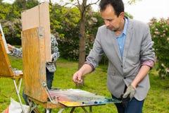 Modny męski artysta miesza farbę z paletteknife podczas Obraz Stock