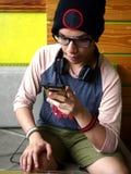 Modny męski nastolatek używa smartphone Zdjęcia Royalty Free