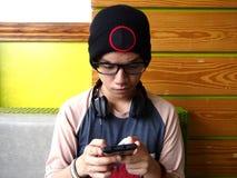 Modny męski nastolatek używa smartphone Fotografia Stock