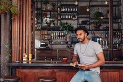 Modny młody męski obsiadanie przy cukiernianym kontuarem z książką Obrazy Royalty Free