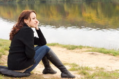 Modny młodej kobiety obsiadanie na brzeg rzeki Fotografia Stock