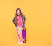 Modny małej dziewczynki dziecko słucha muzyka w hełmofonach Fotografia Stock