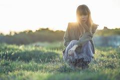 Modny młodej dziewczyny przycupnięcie w zwykłej sukni i kurtce Zdjęcia Royalty Free