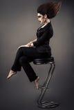 Modny piękny biznesowej kobiety obsiadanie na prętowej stolec z luksusowym włosy i zmroku makeup zdjęcie royalty free