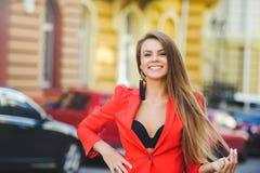 Modny spojrzenie, gorący dnia model młoda kobieta chodzi w mieście, jest ubranym czerwoną kurtkę, blondyn i uśmiechu ove, outdoor Obraz Stock