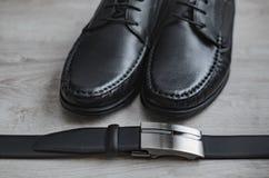 Modo degli uomini Accessori degli uomini Scarpe e cintura nera nere Ancora vita 1 L'affare considera un fondo di legno fotografia stock