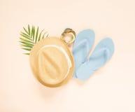 Modo di estate, attrezzatura di estate su fondo crema Flip-flop blu, conchiglia, braccialetto di legno e cappello di paglia Dispo Immagine Stock