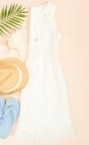 Modo di estate, attrezzatura di estate su fondo crema Vestito bianco dal pizzo, Flip-flop blu e cappello di paglia Disposizione p Fotografie Stock Libere da Diritti