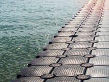 Modo di plastica della passeggiata del pontone che galleggia nel mare immagini stock