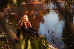 Modo do outono Mulher bonita nova que aprecia o outono no parque na queda fotografia de stock royalty free