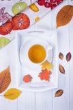 Modo do outono Tisana, folha de bordo do pão-de-espécie e bolotas e folhas de outono secas em um fundo de madeira branco foto de stock