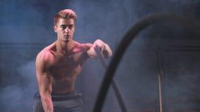 Modo eficaz de la práctica del culturista de quemar calorías Entrenamiento de la cuerda de la batalla en gimnasio almacen de metraje de vídeo