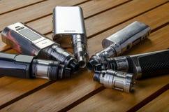Mods électroniques de cigarette pour l'ecig au-dessus d'un fond en bois dispositifs et cigarette de vape photos libres de droits