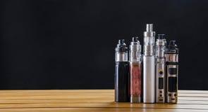 Mods électroniques de cigarette pour l'ecig au-dessus d'un fond en bois dispositifs et cigarette de vape images libres de droits