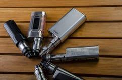 Mods électroniques de cigarette pour l'ecig au-dessus d'un fond en bois dispositifs et cigarette de vape image stock