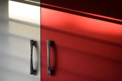 Modular Kitchen cupboard in white and red with sunlight royalty free stock photo