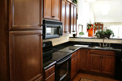 Modules en bois de cuisine noirs et poêle inoxidable Images libres de droits
