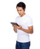 Młody azjatykci mężczyzna use cyfrowa pastylka Obrazy Royalty Free