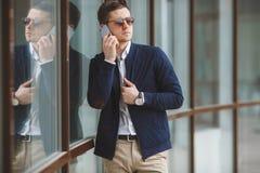 Młody biznesmen opowiada na telefonie komórkowym outdoors Zdjęcia Royalty Free