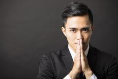 Młody biznesmen z modli się gest Zdjęcia Royalty Free
