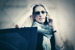 Mody biznesowa kobieta dzwoni na telefonie komórkowym obok samochodu w okularach przeciwsłonecznych Fotografia Royalty Free