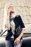 Mody biznesowa kobieta opowiada na telefonie komórkowym obok samochodu w okularach przeciwsłonecznych Fotografia Stock