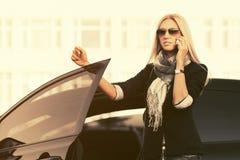 Mody biznesowa kobieta opowiada na telefonie komórkowym na zewnątrz jej samochodu w okularach przeciwsłonecznych Obrazy Royalty Free