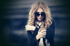 Mody biznesowa kobieta w okularach przeciws?onecznych u?ywa? m?drze telefon na miasto ulicie fotografia stock