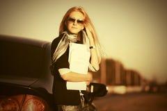 Mody biznesowa kobieta w okularach przeciwsłonecznych obok jej samochodu Zdjęcie Stock