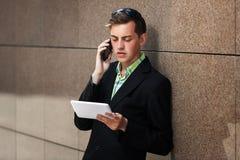 Młody biznesowy mężczyzna dzwoni na telefonie z pastylka komputerem Zdjęcia Royalty Free