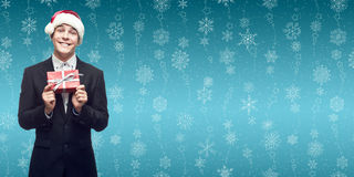 Młody biznesowy mężczyzna w Santa mienia bożych narodzeń kapeluszowym prezencie nad wint Fotografia Royalty Free