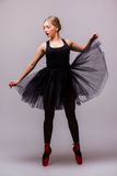 Młody blondynki baleriny dziewczyny taniec i pozować w czarnej spódniczce baletnicy i baletniczych butach na popielatym tle Obraz Stock