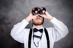 Młody brodaty mężczyzna patrzeje przez lornetki Obrazy Stock