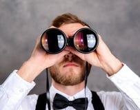 Młody brodaty mężczyzna patrzeje przez lornetki Fotografia Stock