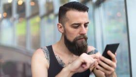 Młody brodaty mężczyzna używa telefon komórkowego Fotografia Royalty Free