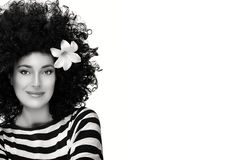 Mody brunetki dziewczyna z kwiatem w Kędzierzawej Afro fryzurze Zdjęcie Royalty Free