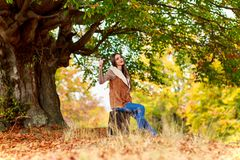 Mody brunetki kobieta z walizką przy jesienią Obrazy Royalty Free